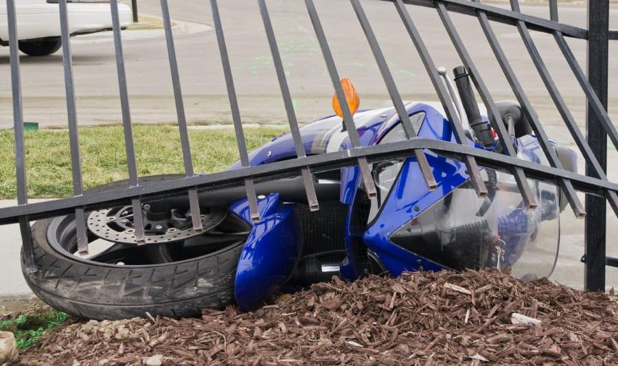 motorcycle crashed under fence