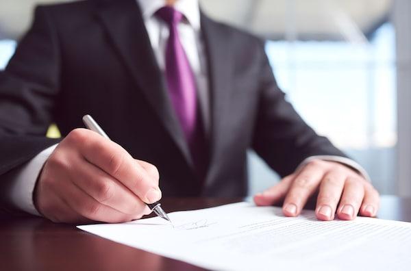 Image of man signing paperwork